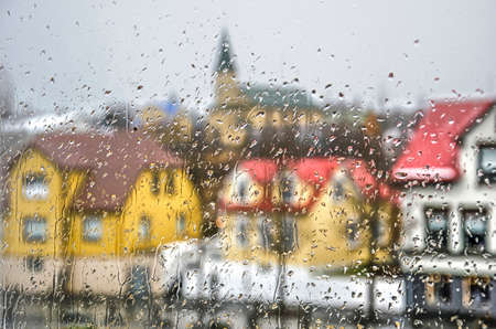 Raindrops on a glass window on a rainy day in Iceland, with  the blurred shapes of traditional colorful houses and a church behind it Stock fotó
