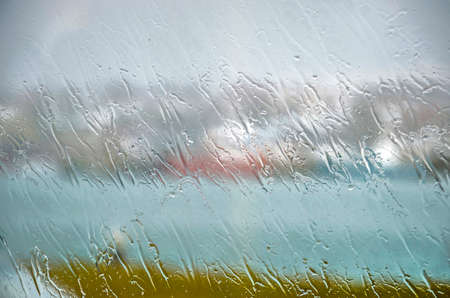 Falling rain creating stripe patterns on the glass of a window on a rainy day in Hafnarfjordur, Iceland, with behind it barely recognizable the blurred shapes of ships and the harbour
