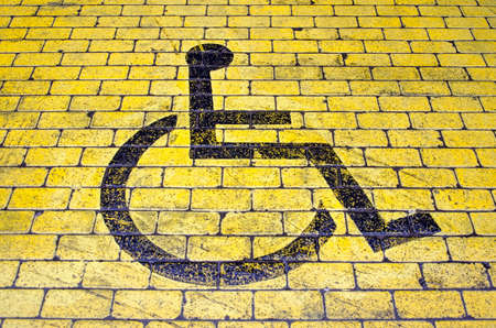 Wheelchair icon in black on yellow pavement indicating a parking place for disabled visitors Stockfoto