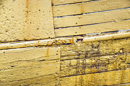Fragment of the hull of an old fishing boat with wooden planks in various sizes, painted yellow, with stains of dirt and rust and other irregularies Stockfoto