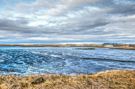 View from the shore at the town of Borgarnes, Iceland, towards the adjacent mudflats, the ocean and the land beyond, under a dramtic cloudy sky Stockfoto