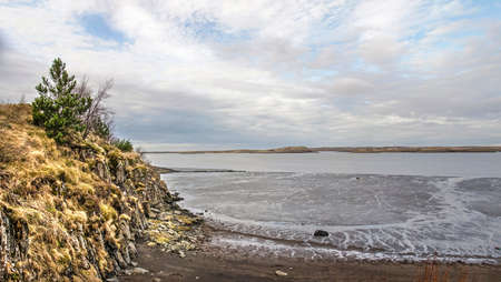 Low cliff with dry grass and bushes, facing a sandy beach. mudflats and a fjord at the town of Borgarnes, Iceland