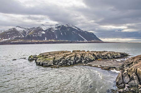 Low rock formation on the shore at the town of Borgarnes, Iceland, with a view towards the fjord, the snow-capped mountains and the ocean beyond