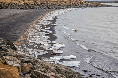 Large chuncks of ice on the black sandy beach of a little bay at a fjord near the town of Borgarnes, Iceland in winter