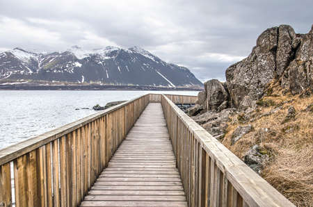 Wooden pedestrian walkway around a cliff at the bank of a fjord near the town of Borgarnes, Iceland