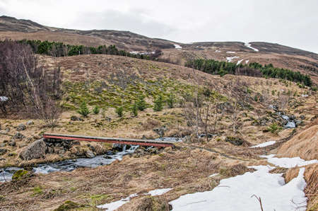 Icelandic landscape in late winter with a narrow wooden bridge across a small brook with small waterfalls and rapids