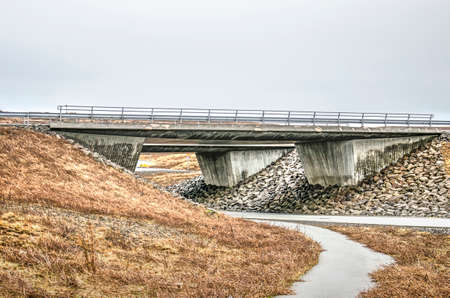 Robust concrete viaduct in a highway near Reykjavik, Iceland, with a secondary road passing underneath
