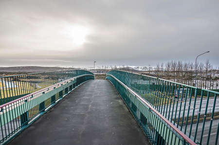 Pedestrian and bicycle bridge with an asphalt surface across a highway near Reykjavik, Iceland under a cloudy sky Stockfoto
