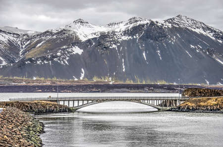 Concrete arch bridge connecting the town of Borgarnes in Iceland with Brakarey island, with the fjord and the mountains in the background