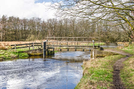 Wooden pedestrian bridge in a hiking trail across the river Dommel near Valkenswaard, The Netherlands on a nice day in springtime Stockfoto