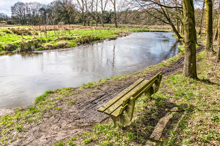 Wooden bench along a muddy trail on the bank of the river Dommel near Valkenswaard, The Netherlands on a sunny day in springtime