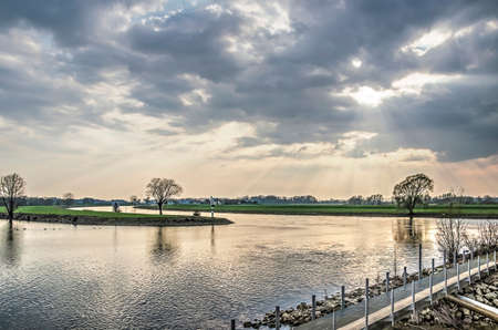 Dramatic skies over the IJssel river and the land beyond as seen from the waterfront of the town of Doesburg, The Netherlands