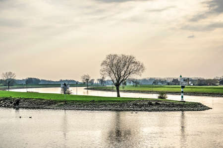 Meadows and scattered trees near a gentle curve in the river IJssel as seen from the waterfront of the town of Doesburg, The Netherlands, with the Old IJssel river in the foreground