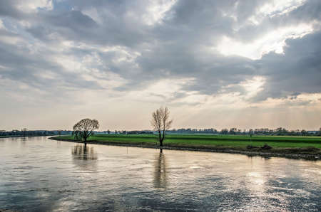 Looking upstream at the IJssel river from the waterfront of the town of Doesburg, The Netherlands under a dramatic sky on an afternoon in springtime