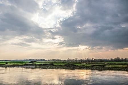 Looking out from the waterfront of the town of Doesburg, The Netherlands towards a spectacular sky reflecting in the water of the IJssel river Stockfoto