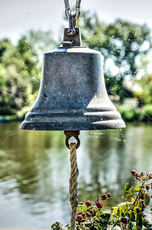 Cobweb-coverd iron bell in brigh sunlight, intended to summon the pedestrian ferry from the other side of a lake in Waterland near Amsterdam Фото со стока