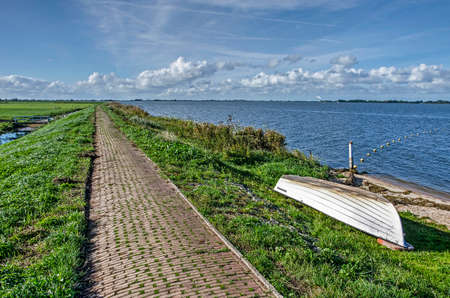Narrow brick path on a low grassy levee along lake Gouwzee on the island of Marken, The Netherlands under a blue sky Stockfoto