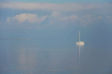 Little sailing yacht on a smotth watersurface at Oosterschelde estuary, the Netherlands on a somewhat hazy day
