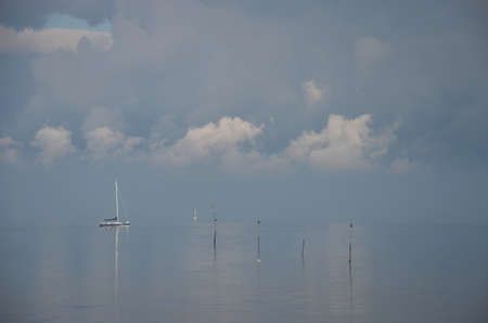 Minimalist image of a hazy day at Oosterschelde estuary, the Netherlands with a little sailing yacht, dramatic clouds, and wooden poles Stockfoto
