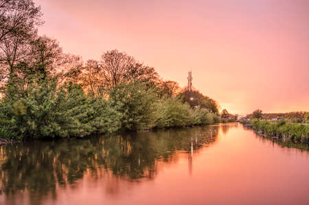 Raindrops created by a slight drizzle in a Dutch canal with trees and bushes on one side and reeds and grass on the other under a spectacular purple sky at sunset