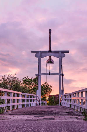 Traditional white wooden drawbridge across a Dutch canal with a spectacular purplish cloudy sky in the backgroound