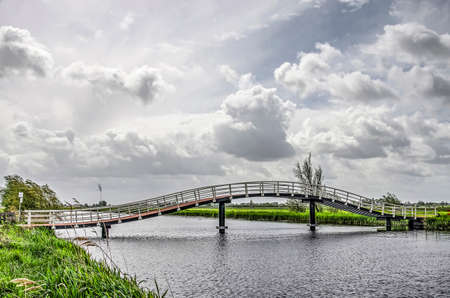 Curving pedestrian bridge across Ammersche Boezem canal in the Alblasserwaard polder in the Netherlands under a dramatic sky in springtime