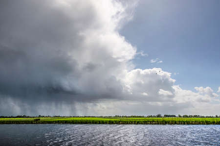 Rain shower dropping its loads over the Alblasserwaard polder in the Netherlands followed by a bright interval 版權商用圖片