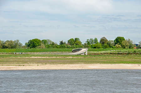 View across the river Waal near Nijmegen, The Netherlands towards the floodplains, beach and Zaligebrug pedestrian bridge on the oppostie bank