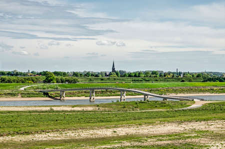 View across the floodplains of the river Waal near Nijmegen, The Netherlands with the Zaligebrug pedestrian bridge across the new river Channel and the church tower of Lent in the distance Stockfoto