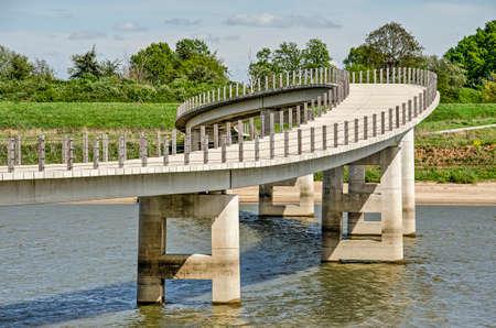 The playfully meandering concrete Zaligebrug pedestrian bridge across the new river channel in the floodplains of the river Waal near Nijmegen, The Netherlands
