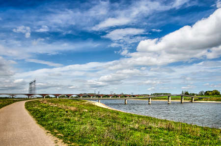 Floodplains of the river Waal near Nijmegen, The Netherlands with the new river channel, a parallel footpath and in the distance the Zaligebrug and Oversteek bridges