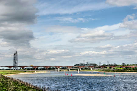The new channel of the river Waal near Nijmegen, The Netherlands with a sandy island and in the distance two bridges under a friendly sky