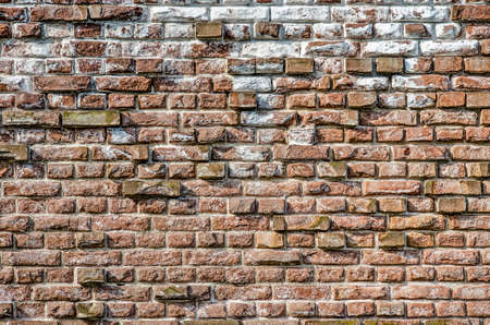 Old masonry wall with chalk and other impurities and with protruding bricks forming an irregular relief pattern Stok Fotoğraf