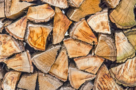 Pile of logs next to a fireplace