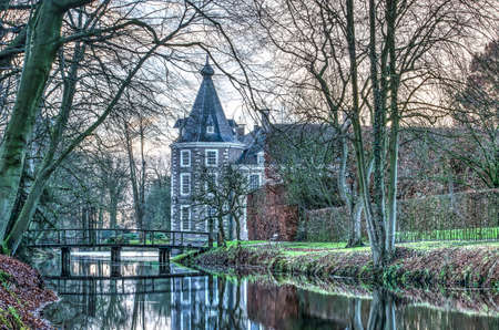 Heino, The Netherlands, December 12, 2017: part of Nijenhuis castle, nowadays in use as a museum, and the surrounding gardens and canals on a late afternoon in winter