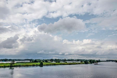 Dramatic clouds over the river Maas and the landscape beyond packed with lakes and marinas near Roermond, The Netherlands