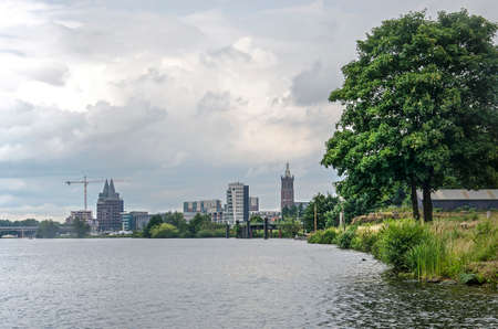 View along the banks of the river Maas towards the skyline of Roermond, The Netherlands with Saint Christoffers cathedral and some more recent highrise