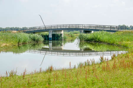 Concrete bridge for pedestrians and cyclists across a creek in the Noordwaard section of Biesbosch national park in the Netherlands on a sunny day in summer Banco de Imagens