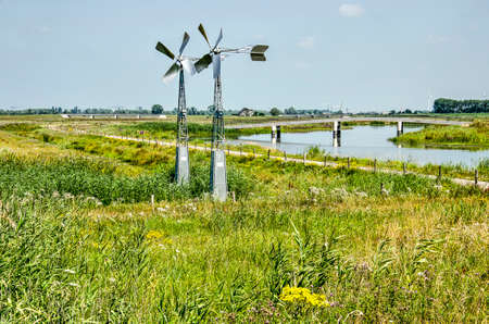 Landscape in the Noordwaard section of Biesbosch national park in the Netherlands, with two small steel windmills, a cycle path, a creek and a bridge on a summer day