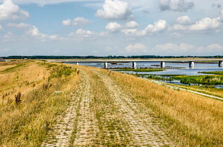 Footpath made of haf open bricks on a grassy dike along Reevediep fllod channel near Kampen, The Netherlands with a concrete bridge in the background