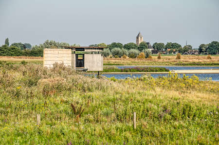 Wooden birdwatching hut at Vreugerijkerwaard nature reserve near Zwolle, the Netherlands on a sunny morning in summer, with the church of Zalk in the background