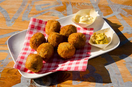 White plate with bitterballen (traditional Dutch meat balls), mayonaise and mustard on a sunlit wooden table Editorial