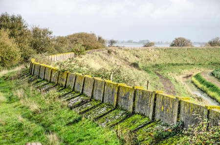 Grassy dike on the north coast of the island of Schouwen-Duiveland, The Netherlands with the weathered concrete of the former sea defense