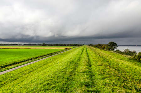 Dramatic dark clouds over a vast landscape on the island of Schouwen-Duiveland, The Netherlands, with a grassy dike, green fields and lake Grevelingen