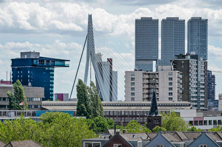 Rotterdam, The Netherlands, June 2, 2019: view across the rooftops of the neighbourhood of Cool towards the Nieuwe Maas riverfront with Inntel hotel, Erasmus bridge and De Rotterdam building Editorial
