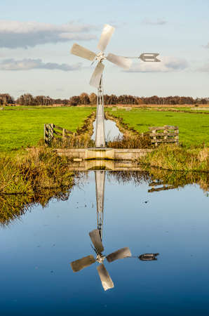 Small modern steel windmill reflecting in the smooth water of a canal ina polder in the Green Heart of the Netherlands near the town of Bodegraven on a sunny day