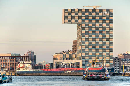 Rotterdam, The Netherlands, December 3, 2019: view across the river Nieuwe Maas with the passenger ferry in front of the striking building of the Shipping and Transport College