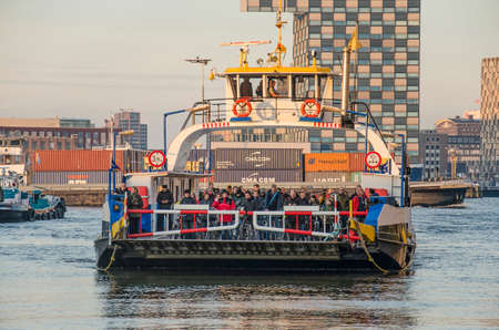 Rotterdam, The Netherlands, December 3, 2019: the temporary ferry for pedestrians and cyclists approaching the jetty in Sint Jan's Harbour Editorial
