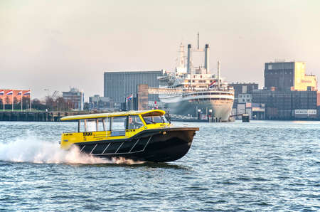 Rotterdam, The Netherlands, December 3, 2019: rapid yellow and black watertaxi on the river Nieuwe Maas with historic cruise ship SS Rotterdam and Maashaven harbour in the background