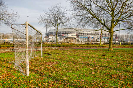 Rotterdam, The Netherlands, November 24, 2019: white steel football goal on a field covered with leaves in Feijenoord neigbourhood, with Feyenoord stadium De Kuip in the background